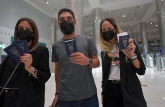 Israelis pose for a picture with their passports upon arrival from Tel Aviv to the Dubai airport in the United Arab Emirates, on November 26, 2020, on the first scheduled commercial flight operated by budget airline flydubai, following the normalisation of ties between the UAE and Israel. (Photo by Karim SAHIB / AFP) (Photo by KARIM SAHIB/AFP via Getty Images)
