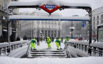epa08927990 Workers plow snow for people to walk through at Gran Via Avenue in Madrid, Spain, 09 January 2021. Storm Filomena brought the heaviest snowfall in decades.  EPA/BALLESTEROS