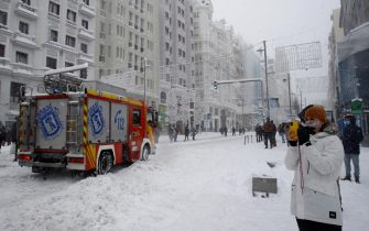 epa08927718 People walk on the snow in Gran Via Avenue in Madrid, Spain, 09 January 2021. Storm Filomena brought the heaviest snowfall in decades.  EPA/BALLESTEROS