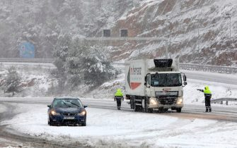 epa08927652 Catalan Mossos d'Esquadra police officers stop a truck in El Bruc (Barcelona), Spain, 09 January 2021. Storm Filomena brought the heaviest snowfalls in decades in the country.  EPA/SUSANNA SAEZ