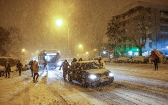 epa08927547 People push a car stranded in the snow in Madrid, Spain, late 08 January 2021. A red warning has been issued in Madrid as storm Filomena brought the heaviest snowfall in decades.  EPA/Rodrigo Jimenez