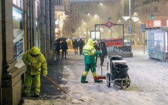 epa08927267 Workers shovel snow at the Gran Via, central Madrid, Spain on 08 January 2021. A red warning has been issued in Madrid because of heavy snowfalls expected due to storm Filomena that has already caused a big drop in temperatures and snowfalls throughout Spain.  EPA/RODRIGO JIMENEZ