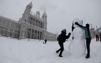 epa08928018 People build a snowman near the Almudena Cathedral in Madrid, Spain, 09 January 2021. Storm Filomena brought the heaviest snowfall in decades.  EPA/David Fernandez