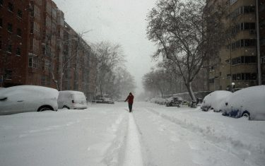 epa08927580 A woman walks through a snow-covered street in Madrid, Spain, 09 January 2020. Storm Filomena brought the heaviest snowfall in decades.  EPA/BALLESTEROS