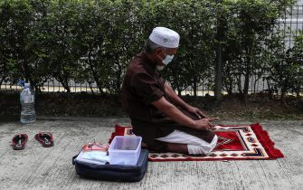 epa08932451 A Muslim man prays on a roadside in Kuala Lumpur, Malaysia, 12 January 2021. According to media reports on 12 January, the King of Malaysia declared a state of emergency in the country in an attempt to halt the spread of the coronavirus disease (COVID-19) pandemic. The state of emergency will last until 01 August, but can be lifted earlier if infection rates decrease.  EPA/FAZRY ISMAIL