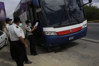 RIO HONDO, GUATEMALA - JANUARY 18: Police officers check a bus at a registration booth on January 18, 2021 in Rio Hondo, Zacapa, Guatemala. The caravan departed from Honduras to walk across Guatemala and Mexico to eventually reach the United States. After clashing with the police yesterday migrants are being held to carry out immigration and heath controls. Central Americans expect to receive asylum and most Hondurans decided to migrate after being hit by recent hurricanes.  (Photo by Josue Decavele/Getty Images)