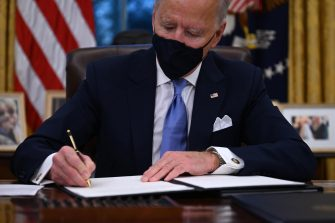 US President Joe Biden signs a series of orders in the Oval Office of the White House in Washington, DC, after being sworn in at the US Capitol on January 20, 2021. (Photo by Jim WATSON / AFP)