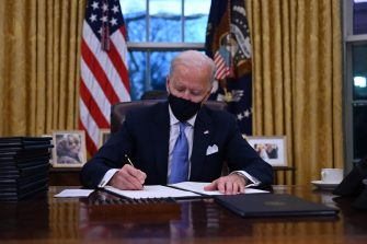 TOPSHOT - US President Joe Biden sits in the Oval Office as he signs a series of orders at the White House in Washington, DC, after being sworn in at the US Capitol on January 20, 2021. - US President Joe Biden signed a raft of executive orders to launch his administration, including a decision to rejoin the Paris climate accord. The orders were aimed at reversing decisions by his predecessor, reversing the process of leaving the World Health Organization, ending the ban on entries from mostly Muslim-majority countries, bolstering environmental protections and strengthening the fight against Covid-19. (Photo by Jim WATSON / AFP)