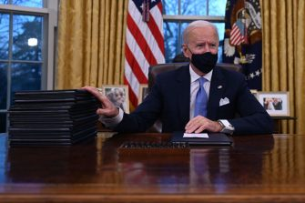 US President Joe Bidenprepares to sign a series of orders in the Oval Office of the White House in Washington, DC, after being sworn in at the US Capitol on January 20, 2021. - US President Joe Biden signed a raft of executive orders to launch his administration, including a decision to rejoin the Paris climate accord. The orders were aimed at reversing decisions by his predecessor, reversing the process of leaving the World Health Organization, ending the ban on entries from mostly Muslim-majority countries, bolstering environmental protections and strengthening the fight against Covid-19. (Photo by Jim WATSON / AFP) (Photo by JIM WATSON/AFP via Getty Images)