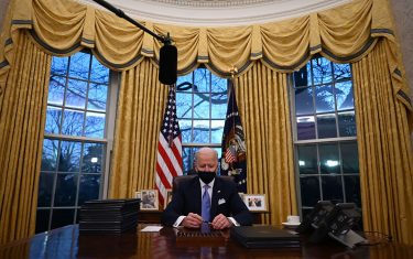 TOPSHOT - US President Joe Biden holds a pen as he prepares to sign a series of orders in the Oval Office of the White House in Washington, DC, after being sworn in at the US Capitol on January 20, 2021. - US President Joe Biden signed a raft of executive orders to launch his administration, including a decision to rejoin the Paris climate accord. The orders were aimed at reversing decisions by his predecessor, reversing the process of leaving the World Health Organization, ending the ban on entries from mostly Muslim-majority countries, bolstering environmental protections and strengthening the fight against Covid-19. (Photo by Jim WATSON / AFP) (Photo by JIM WATSON/AFP via Getty Images)