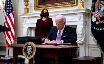 epa08956525 US President Joe Biden signs an executive order after speaking during an event on his administration's Covid-19 response with U.S. Vice President Kamala Harris, left, in the State Dining Room of the White House in Washington, DC, USA, on 21 January 2021. Biden in his first full day in office plans to issue a sweeping set of executive orders to tackle the raging Covid-19 pandemic to rapidly reverse or refashion many of his predecessor's most heavily criticized policies.  EPA/Al Drago / POOL