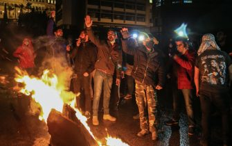 epa08971512 Anti-government protesters stand around burning objects as they protest against the lockdown in front the government palace in Beirut, Lebanon, 28 January 2021. Protesters gathered against the deteriorating economic situation after Lebanon began on 07 January a complete 25-day closure nationwide, which was extended by the Supreme Defense Council until 08 February, to curb the spread of the Sars-CoV-2 coronavirus.  EPA/NABIL MOUNZER