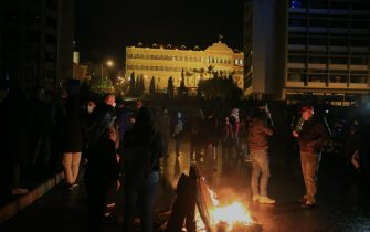 epa08971510 Anti-government protesters stand around burning objects as they protest against the lockdown in front the government palace in Beirut, Lebanon, 28 January 2021. Protesters gathered against the deteriorating economic situation after Lebanon began on 07 January a complete 25-day closure nationwide, which was extended by the Supreme Defense Council until 08 February, to curb the spread of the Sars-CoV-2 coronavirus.  EPA/NABIL MOUNZER