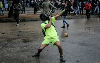 28 January 2021, Lebanon, Tripoli: An anti-government activist hurls rocks with a slingshot against riot police near Serail (headquarters of the Governorate) during a protest against the bad economical situations that the country facing amid a national coronavirus lockdown to curb the spread of the coronavirus pandemic. A man lost his life and at least 200 people got injured in the past couple of days due to the ongoing demonstrations. Photo: Marwan Naamani/dpa