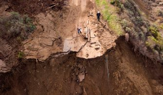 Workers assess the scene where a section of Highway 1 collapsed into the Pacific Ocean near Big Sur, California on January 31, 2021. - Heavy rains caused debris flows of trees, boulders and mud that washed out a 150-foot section of the road. (Photo by JOSH EDELSON / AFP) (Photo by JOSH EDELSON/AFP via Getty Images)
