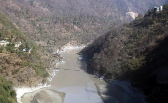 epa08995387 View of the overflowed Mandakini river, a tributary of the Alaknanda River, near the Rudraprayag district in Uttarakhand, India, 08 February 2021. At least 11 people died and nearly 150 are still missing after part of the Nanda Devi glacier fell into the river, triggering a flood that burst open a dam in the Tapovan area of Uttarakhand's Chamoli district on 07 February 2021.  EPA/RAJAT GUPTA