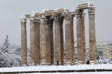 epa09015843 Employees make their way in the archaeological site of the Temple of Zeus during heavy snowfall, in Athens, Greece, 16 February 2021. As the cold front Medea sweeping over Greece was in full progress and heading south, very low temperatures were recorded in the northern parts of the country.  EPA/ORESTIS PANAGIOTOU