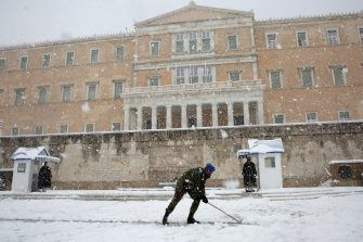epa09015839 Military personel clean the area at the Monument of Unknown Soldier in front of the Greek Parliament during heavy snowfall, in Athens, Greece, 16 February 2021. As the cold front Medea sweeping over Greece was in full progress and heading south, very low temperatures were recorded in the northern parts of the country.  EPA/ORESTIS PANAGIOTOU