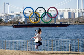 epa09003394 A young girl jumps a rope in front of a giant Olympic rings monument at Odaiba Marine Park in Tokyo, Japan, 11 February 2021. Tokyo 2020 Olympic Games Organising Committee President Yoshiro Mori is to step down following the turmoil caused by the sexist remarks he made on 03 February during a Japanese Olympic Committee meeting.  EPA/FRANCK ROBICHON