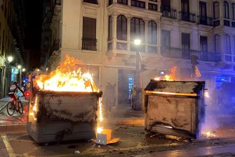 epa09020404 Garbage bins burn during a protest to condemn the imprisonment of Spanish rapper Pau Rivadulla Duro A.K.A 'Pablo Hasel', in Barcelona, Spain, 17 February 2021. Hasel was given a nine-month-prison sentence late January after the Supreme Court found him guilty of incitement to terrorism and offense against the dignity of the Spanish Crown and State institutions on his lyrics.  EPA/Enric Fontcuberta