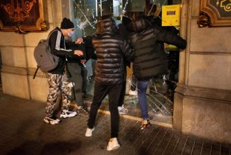 epa09020414 Protesters vandalize a shop during riots to condemn the imprisonment of Spanish rapper Pau Rivadulla Duro A.K.A 'Pablo Hasel', in Barcelona, Spain, 17 February 2021. Hasel was given a nine-month-prison sentence late January after the Supreme Court found him guilty of incitement to terrorism and offense against the dignity of the Spanish Crown and State institutions on his lyrics.  EPA/Enric Fontcuberta