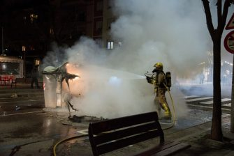 epa09020416 A fireman puts out a fire at a garbage container during a protest to condemn the imprisonment of Spanish rapper Pau Rivadulla Duro A.K.A 'Pablo Hasel', in Barcelona, Spain, 17 February 2021. Hasel was given a nine-month-prison sentence late January after the Supreme Court found him guilty of incitement to terrorism and offense against the dignity of the Spanish Crown and State institutions on his lyrics.  EPA/Enric Fontcuberta