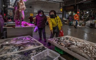 epa08957080 Woman wearing protective face masks chose fish at a market in a residential area of Wuhan, China, 22 January 2021. The day 23 January 2021 marks the one-year anniversary of the start of a strict 76-day lockdown of the Chinese city of Wuhan where the coronavirus was first discovered before spreading across the world into a deadly global pandemic.  EPA/ROMAN PILIPEY