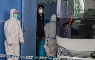TOPSHOT - Vladimir G. Dedkov (C), a member of the World Health Organization (WHO) team investigating the origins of the Covid-19 pandemic, boards a bus following the team's arrival at a cordoned-off section in the international arrivals area at the airport in Wuhan on January 14, 2021. (Photo by NICOLAS ASFOURI / AFP)