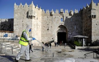 A municipal worker disinfects in front of the Damascus Gate in Jerusalem's Old City as a measure against the spread of coronavirus (COVID-19), on March 29, 2020. (Photo by Ahmad GHARABLI / AFP)