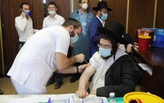 epa09004309 An Ultra orthodox Jewish man receives a COVID-19 vaccine from a nurse at Ichilov Medical Center in a Yeshiva at the Ultra orthodox city of Bnei Brak, Israel, 11 February 2021. Israel begin a vaccinations campaign at the ultra orthodox community, as Israel has so far vaccinated over three million of its around nine million citizens with the first dose of the coronavirus and two million have been given the second dose  EPA/ABIR SULTAN