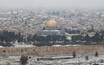 epa09020431 General view of the Dome of the Rock covered in snow, in the old city of Jerusalem, Israel, 18 February 2021.  EPA/ABIR SULTAN