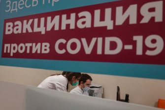 epa08983838 Medics work behind the sign reading 'Vaccination against COVID-19 is carried out here' at the vaccination point at the Columbus shopping mall in Moscow, Russia, 03 February 2021. Russia began a program for mass vaccination against COVID-19 disease, caused by SARS-CoV-2 coronavirus, using the Sputnik V vaccine from January 19. About 8.2 million doses of coronavirus vaccines have been released in Russia. More than 420 thousand people were vaccinated in Moscow. The number of vaccination stations in Russia is growing rapidly: in about a week it increased almost one and a half times - from 2.25 thousand to 3.1 thousand.  EPA/SERGEI ILNITSKY