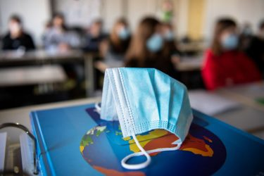 17 November 2020, Bavaria, Munich: ILLUSTRATION - A mouth and nose protector is in the classroom in a geography seminar in grade 11 at the state grammar school Trudering on a world atlas, while in the background the students with mouth and nose protectors can be seen. Photo: Matthias Balk/dpa (Photo by Matthias Balk/picture alliance via Getty Images)