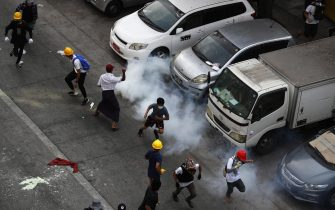 epa09048020 Demonstrators react as tear gas is fired by police during a protest against the military coup in Yangon, Myanmar, 03 March 2021. Foreign ministers of the Association of Southeast Asian Nations (ASEAN) called for a halt of violence during a meeting on 02 March as protests continued amid rising tension in the country between anti-coup protesters and security forces.  EPA/NYEIN CHAN NAING