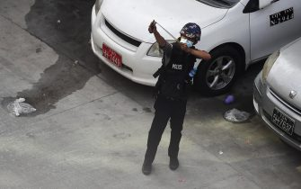 epa09048047 A policeman aims a slingshot at protesters during a protest against the military coup in Yangon, Myanmar, 03 March 2021. Foreign ministers of the Association of Southeast Asian Nations (ASEAN) called for a halt of violence during a meeting on 02 March as protests continued amid rising tension in the country between anti-coup protesters and security forces.  EPA/NYEIN CHAN NAING