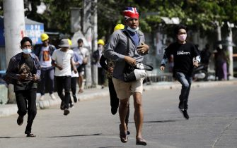 epa09050437 Demonstrators flee after seeing military trucks during an anti-coup protest in Yangon, Myanmar, 04 March 2021. The United Nations said at least 38 people were killed on 03 March in the bloodiest crackdown yet by the military. More than 50 people have died in Myanmar since the coup started on 01 February 2021.  EPA/LYNN BO BO