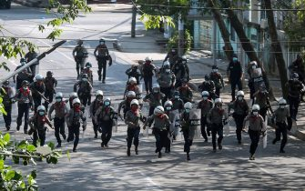 Police run towards protesters to disperse a demonstration being held against the military coup in Yangon on March 3, 2021. (Photo by STR / AFP)