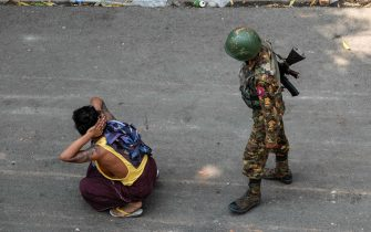 TOPSHOT - A soldier stands next to a detained man during a demonstration against the military coup in Mandalay on March 3, 2021. (Photo by STR / AFP)