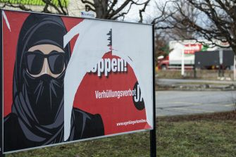 epa09056964 (FILE) - A torn poster of the initiative 'Yes to the burqa-ban' is seen in Thun, Switzerland, 05 February 2021 (reissued 06 March 2021). Swiss citizens are called on Sunday 7 March to vote on a proposal to prohibit the concealment of one's face in the public space. Led by right-wing groups, the so-called 'anti-burqa' initiative provides for a ban on the wearing of the niqab, as well as other non-religious forms of face concealment.  EPA/PETER SCHNEIDER