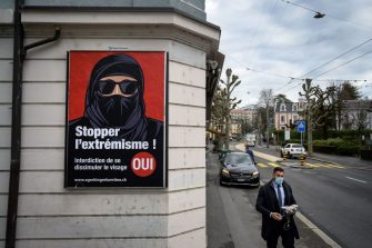 """A man wearing a face mask walks on February 4, 2021 in Lausanne past an electoral poster in favor of a """"burqa ban"""" initiative reading in French: """"Stop extremism!"""" ahead of a nationwide vote by Swiss citizen on whether they want to ban face coverings in public spaces or not. - The vote will take place on on March 7, 2021, as part of the country's famous direct democratic system. A clear majority of Swiss voters favour introducing a nationwide prohibition against wearing face-covering garments in public spaces, known as a """"burqa ban"""", a poll showed last month. (Photo by Fabrice COFFRINI / AFP) (Photo by FABRICE COFFRINI/AFP via Getty Images)"""
