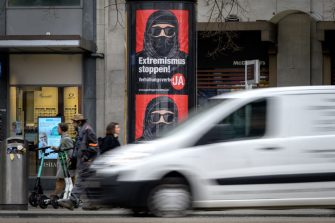"""Pedestrians walk past campaign posters, in favour of the """"burqa ban"""" initiative reading in German: """"Stop extremism!"""" on March 3, 2021 in the streets of Zurich, ahead of a nationwide vote on March 7, 2021 by Swiss citizen on whether to ban full facial coverings in public places. - Polls indicate a majority support the move, in a vote that comes after years of debate following similar bans in other European countries -- and in some Muslim-majority states. (Photo by Fabrice COFFRINI / AFP) (Photo by FABRICE COFFRINI/AFP via Getty Images)"""