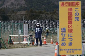 """A sign for a """"difficult-to-return"""" designated zone is displayed next to a security officer standing guard in front of bags of contaminated soil in Namie, Fukushima Prefecture, Japan, on Monday, March 8, 2021. Laid waste by a nuclear disaster a decade ago, Japans Fukushima is still struggling to recover, even as the government tries to bring people and jobs back to former ghost towns by pouring in billions of dollars to decontaminate and rebuild. Photographer: Toru Hanai/Bloomberg via Getty Images"""