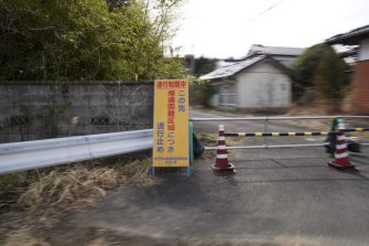 """A sign for a """"difficult-to-return"""" designated zone is displayed next to a gate in Namie, Fukushima Prefecture, Japan, on Monday, March 8, 2021. Laid waste by a nuclear disaster a decade ago, Japans Fukushima is still struggling to recover, even as the government tries to bring people and jobs back to former ghost towns by pouring in billions of dollars to decontaminate and rebuild. Photographer: Toru Hanai/Bloomberg via Getty Images"""