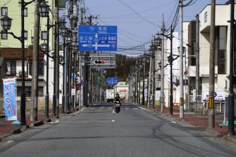 A motorcycle travels along a deserted street in Namie, Fukushima Prefecture, Japan, on Tuesday, March 9, 2021. Laid waste by a nuclear disaster a decade ago, Japans Fukushima is still struggling to recover, even as the government tries to bring people and jobs back to former ghost towns by pouring in billions of dollars to decontaminate and rebuild. Photographer: Toru Hanai/Bloomberg via Getty Images