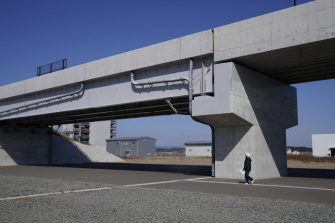 A worker walks under a mock-up bridge at the Fukushima Robot Test Field in Minamisoma, Fukushima Prefecture, Japan, on Tuesday, March 9, 2021. Laid waste by a nuclear disaster a decade ago, Japans Fukushima is still struggling to recover, even as the government tries to bring people and jobs back to former ghost towns by pouring in billions of dollars to decontaminate and rebuild. Photographer: Toru Hanai/Bloomberg via Getty Images