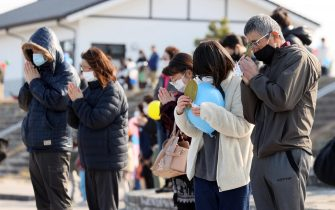 epa09066859 People observe a moment of silent prayers for the victims of the devastating 2011 earthquake and tsunami in Soma, Fukushima prefecture, northeastern Japan, 11 March 2021. Japan is commemorating the 10th anniversary of the Great East Japan Earthquake and subsequent tsunami in which approximately 20,000 people lost their lives on 11 March 2011.  EPA/JIJI PRESS JAPAN OUT EDITORIAL USE ONLY/  NO ARCHIVES