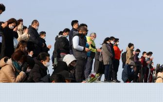 epa09066870 People observe a moment of silent prayers for the victims of the devastating 2011 earthquake and tsunami at Arahama district in Sendai, Miyagi prefecture, northeastern Japan, 11 March 2021. Japan is commemorating the 10th anniversary of the Great East Japan Earthquake and subsequent tsunami in which approximately 20,000 people lost their lives on 11 March 2011.  EPA/JIJI PRESS JAPAN OUT EDITORIAL USE ONLY/  NO ARCHIVES