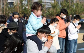epa09066869 People observe a moment of silent prayers for the victims of the devastating 2011 earthquake and tsunami in Ishinomaki, Miyagi prefecture, northeastern Japan, 11 March 2021. Japan is commemorating the 10th anniversary of the Great East Japan Earthquake and subsequent tsunami in which approximately 20,000 people lost their lives on 11 March 2011.  EPA/JIJI PRESS JAPAN OUT EDITORIAL USE ONLY/  NO ARCHIVES