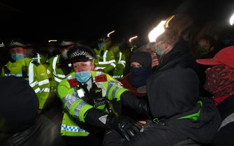 Police scuffle with people gathering at the band-stand where a planned vigil in honour of murder victim Sarah Everard, which was officially cancelled due to Covid-19 restrictions, was to take place on Clapham Common, south London on March 13, 2021. - The police officer charged with murdering young Londoner, Sarah Everard, who disappeared while walking home from a friend's house, appeared in court on March 13, 2021, as organisers cancelled a vigil in her honour due to coronavirus restrictions. (Photo by JUSTIN TALLIS / AFP) (Photo by JUSTIN TALLIS/AFP via Getty Images)