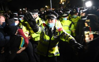LONDON, ENGLAND - MARCH 13: Police officers attend a vigil on Clapham Common, where floral tributes have been placed for Sarah Everard on March 13, 2021 in London, England. Vigils are being held across the United Kingdom in memory of Sarah Everard. Yesterday, the Police confirmed that the remains of Ms Everard were found in a woodland area in Ashford, a week after she went missing as she walked home from visiting a friend in Clapham. Metropolitan Police Officer Wayne Couzens has been charged with her kidnap and murder. (Photo by Leon Neal/Getty Images)